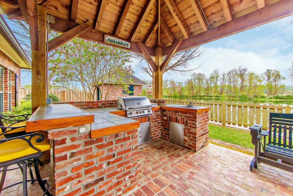 Zděná cihlová zahradní kuchyně pod pergolou s vestavěným grilem